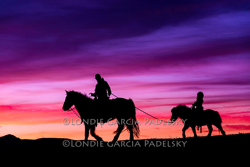 Silhouetted cowboy riding horseback leads young cowgirl on pony at sunset.