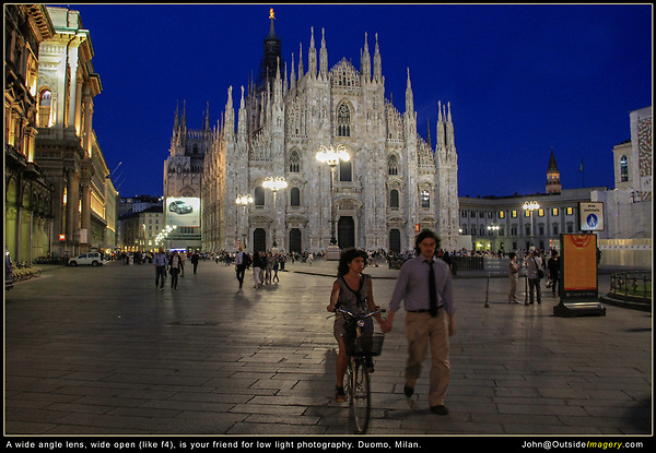 Italy, Milan.  Low Light Photography.<br /> Sometimes you have to accept that not every photo will be sharp. Here it might be a good thing. I can barely see the scowls on their faces. Not everyone wants to be photographed, sorry. <br /> Locals walking through the tourists at the Duomo Cathedra.