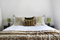 A double bed dressed with a brown and white fur throw and cushions in earthy tones with highlights of light green