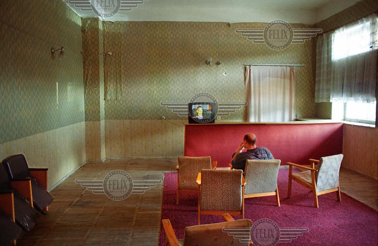 A man watches TV in Jermuk sanatorium.