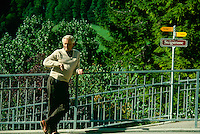 Older man checks his watch while waiting for his companion on a  German walkway