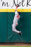 Roberto Lopez (20) of the Arkansas Travelers gets his glove on a hard hit ball over the wall but could not hold on during a game against the Springfield Cardinals on May 10, 2011 at Hammons Field in Springfield, Missouri.  Photo By David Welker/Four Seam Images.
