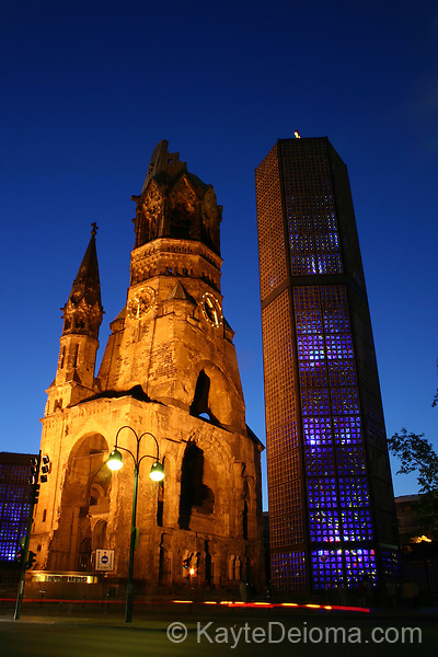 """A late night view of Breitscheidplatz, where the ruined tower of the Kaiser-Wilhelm- Gedaechtniskirche stands next to the new Bell Tower, referred to by locals as the """"Blue Lipstick"""".  Berlin, Germany"""