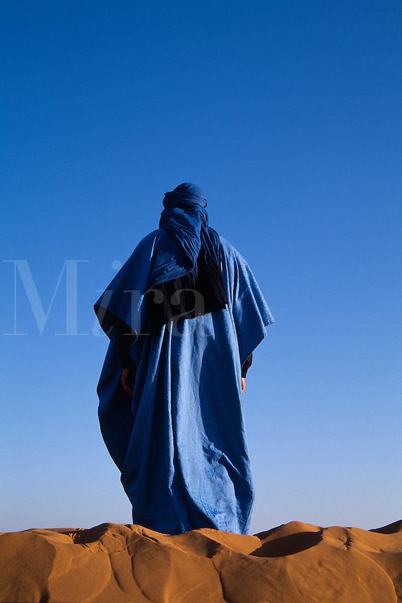 Nomadic male figure wandering alone in the desert, Morocco