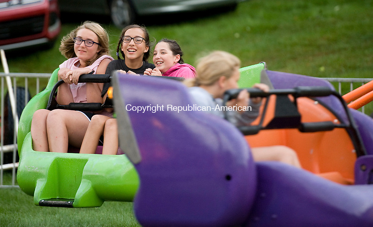 THOMASTON, CT-080217JS05-- Marissa Van Ormer, 12; Julia Bond, 12 and Brenna Albrecht, 11, all from Thomaston, enjoy a ride on &quot;The Sizzler&quot; during opening night of the Thomaston Volunteer Fire Department's annual carnival on Wednesday   The carnival runs through August 5, with fireworks on Friday night and the fireman's parade on Saturday. <br />  Jim Shannon Republican-American