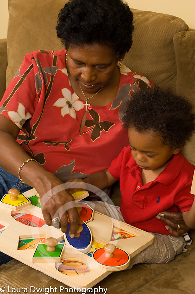 16 month old toddler baby boy child care with great grandmother who takes care of him during the week vertical playing with shape sorting peg puzzle