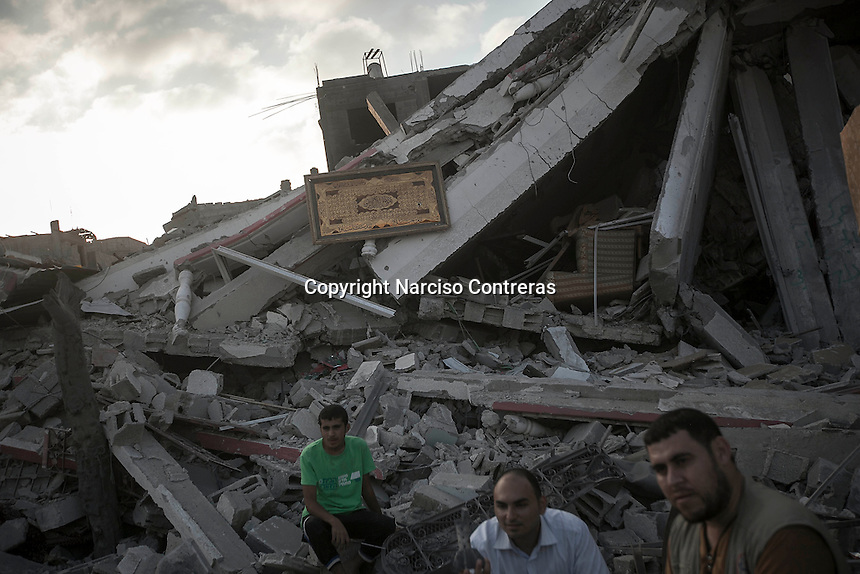 """In this Friday, Aug. 15, 2014 photo, Palestinian men sit at the rubble of a house building destroyed by an israeli airstrike during the """"Protective Edge"""" military operation in Shuyaja neighborhood in Gaza City. After a five days truce was declared on 13th August between Hamas and Israel, civilian population went back to what remains from their houses and goods in Gaza Strip. (Photo/Narciso Contreras)"""