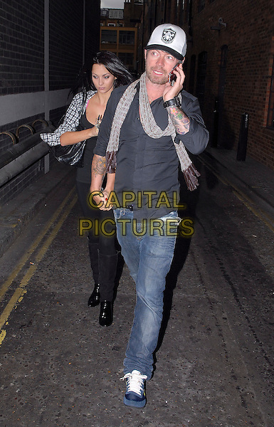 JESSICA JANE CLEMENT & LEE STAFFORD .Spotted in London, England, UK, September 30th 2009..full length couple cap hat scarf grey gray shirt jeans trainers blue talking on phone tattoos holding hands walking black .CAP/IA.©Ian Allis/Capital Pictures.
