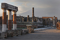 View of the North end of the Forum of Pompeii, the political, commercial and social centre of the town, with the columns of the Temple of Jupiter, built 2nd century BC, and a Memorial Arch, Pompeii, Italy. Pompeii is a Roman town which was destroyed and buried under 4-6 m of volcanic ash in the eruption of Mount Vesuvius in 79 AD. Buildings and artefacts were preserved in the ash and have been excavated and restored. Pompeii is listed as a UNESCO World Heritage Site. Picture by Manuel Cohen