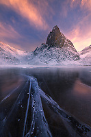 Fluctuations in temperature on a frozen lake cause the ice to expand or contract, making frequent synthetic-like descending tones when new cracks appear.  Here, a series of cracks in an otherwise translucent surface lead to Shark's Tooth peak just as the sun sets below the horizon.