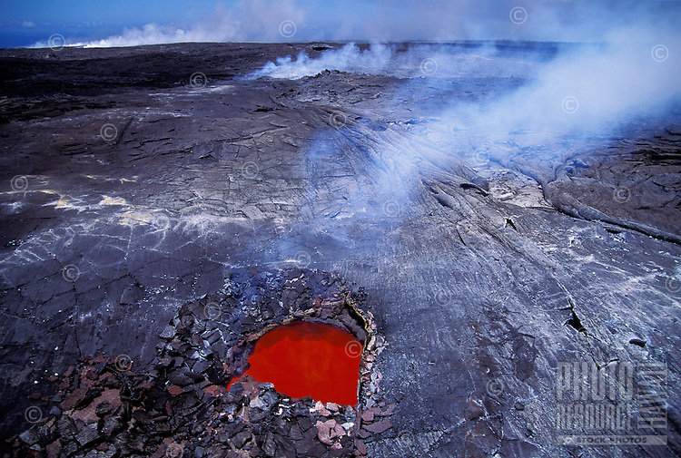 "Fiery """"skylight"""" in lava field, showing volcano flow beneath surface. Puna, Big Island."