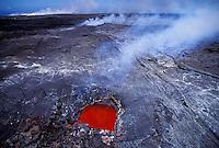"""Fiery """"""""skylight"""""""" in lava field, showing volcano flow beneath surface. Puna, Big Island."""