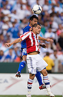 Miguel Samudio (5) of Paraguay goes up for a header with Carlos Ruiz (20) of Guatemala during the game at RFK Stadium in Washington, DC.  Guatemala tied Paraguay, 3-3.