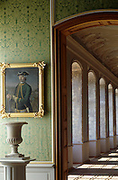A gilt-framed portait hangs against a green damask-covered wall beside a door leading out to a sunlit hallway