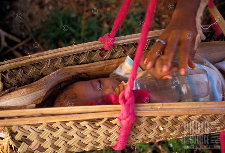 Baby sleeping in a traditioanl cradle being touched by a mothers hand, Yap Micronesia