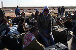 Men wait with their belongings, for busses bound for the airport in Tunis, after crossing into Tunisia at the border crossing with Libya near Ben Guerdane, Tunisia, Thursday, Feb. 24, 2011. Foreign nationals, including many Egyptian workers, fled Libya as Col. Muammar Qaddafi tried to maintain his grip on the capital Tripoli. In the latest uprising to strike the Middle East, street protests which began in Eastern Libya spread to Tripoli, as opposition members called for Qaddafi to follow Tunisian president Zine el-Abidine Ben Ali and Egyptian president Hosni Mubarak and step down.