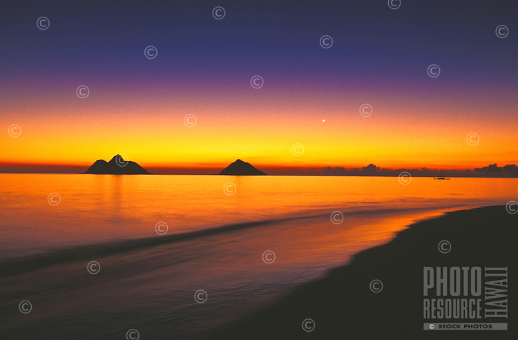 Sunrise on Lanikai beach, with the Moku Lua isands on still morning, windward Oahu