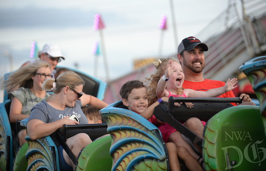 NWA Democrat-Gazette/ANDY SHUPE<br /> Aaron Davis of Tontitown (right) smiles Friday, Aug. 9, 2019, as he rides The Cobra with his daughter, Nora Davis, and son, Hayes Davis, during the 121st Tontitown Grape Festival in Tontitown. The festival, which features crafts vendors, chicken and spaghetti dinners and a midway, continues through today.