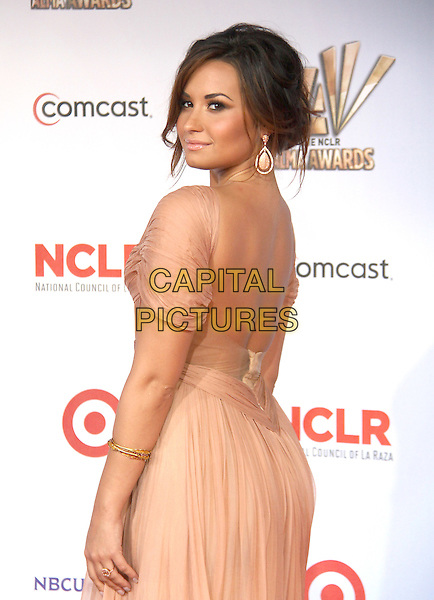 Demi Lovato.at The 2011 NCLR ALMA Awards held at the Santa Monica Civic Auditorium in Santa Monica, California, USA, September 10th 2011.                                                                               .half length dress side over shoulder back rear behind  make-up beauty earrings  beige nude pleated .CAP/RKE/DVS.©DVS/RockinExposures/Capital Pictures.