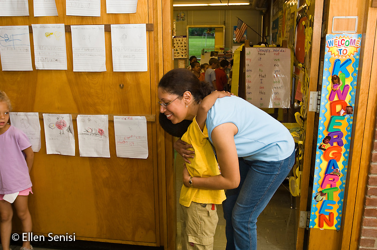 MR / Schenectady, NY. Zoller Elementary School (urban public school). Kindergarten classroom. Paraprofessional (Puerto Rican-American) greets student (boy; age 5; African-American & Puerto Rican-American) at arrival time. MR: Dej2, Cor3. ID: AF-gKb. © Ellen B. Senisi