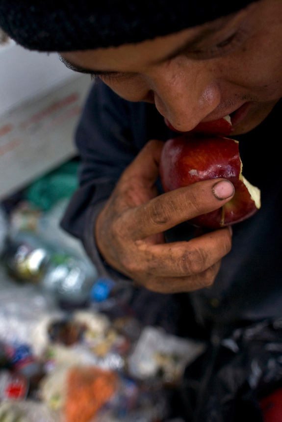 Pepe Padilla finds and eats an apple he discovered in one of the garbage bags colected the wealthy Mexico City neighbourhood of Polanco.  Mexico DF, 09-08-07