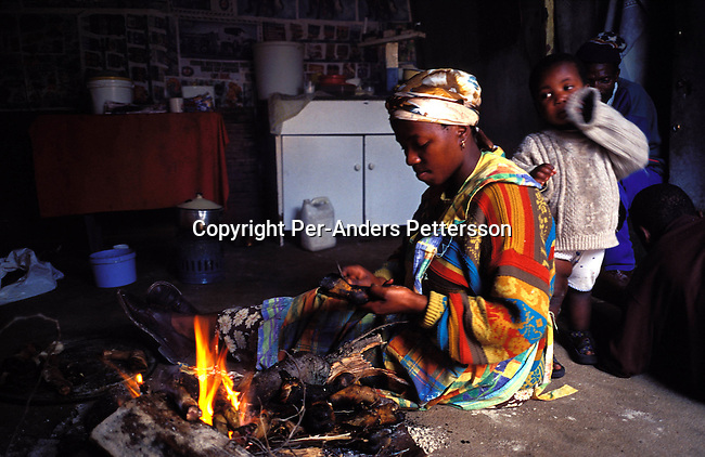 ditown00198 .Digital. Township  An unidentified woman grilling sheep feet in her shack on June 26, 2001 in Site B Khayelitsha, a township about 35 kilometers outside Cape Town, South Africa. She's unemployed and is doing this to earn some extra income for her family of four. Khayelitsha is one of the poorest and fastest growing townships in South Africa. People usually come from the rural areas in Eastern Cape province to find work as maids and laborers. Most people don't find work and the unemployment rate is very high, together with lot of violence and a growing HIV-Aids epidemic itÕs a harsh area to live in. Fire, energy, food children, mother.©Per-Anders Pettersson/iAfrika Photos.