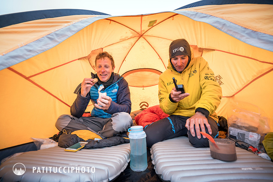 Ueli Steck and David Göttler using satellite phones to communicate their safety while inside advance basecamp tent after Shishapangma