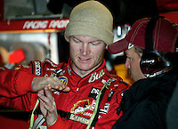 Dale Earnhardt Jr. talks with a crewman in the garage area as he prepares for  the Carolina Dodge Dealers 400 at Darlington Raceway in Darlington, SC on Sunday, 3/16/03.(Photo by Brian Cleary)  The Carolina Dodeg Dealers 400 NASCAR WInston Cup race at Darlington Raceway, Darlington, SC, March 16, 2003.  (Photo by Brian Cleary/www.bcpix.com)