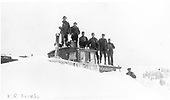 Crew standing atop caboose which is buried in snow.<br /> D&amp;RGW  Cumbres, CO  Taken by Lively, Ken R.