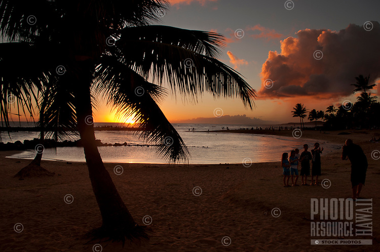 A father taking photos of his children by a palm tree at sunset, Brennecke's Beach, Poipu, Kauai.