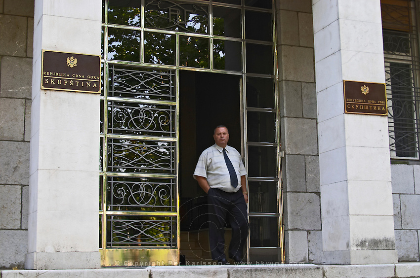 Skupstina Republica Crna Gora, the parliament assembly of Montenegro, main entrance with glass, brass and stone, on the Sveti Petra Saint Peter boulevard. A man walking out of the door. Podgorica capital. Montenegro, Balkan, Europe.