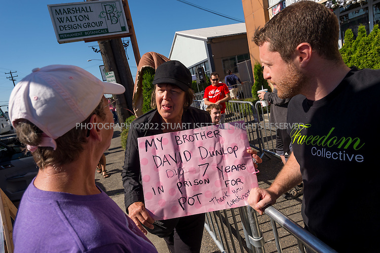 7/8/2014 &mdash; Seattle, Washington<br /> <br /> Donna Dunlop, 60, stands outside Cannabis City, a leaf retail marijuana store in Seattle, WASH., holding a sign about her brother who served time in prison for marijuana crimes.<br /> <br /> Cannabis City, owned by James Lathrop, opened today in Seattle, WASH. one of several legal marijauna retail stores to open across Washington State on July 8th, 2014. Of Washington's 334 marijuana license lottery winners, the Washington State Liquor Control Board issued 24 actual retail licenses for the July 8th deadline.<br /> <br /> Cannabis City expected to have 10 pounds of marijuana stocked for their grand opening, selling for $15 to $20 per gram. Because of timing, many retail pot stores in Washington State will face shortages as legal growing operations ramp up production to meet demand. Lines started forming at Cannibis City the night before it opened.<br /> <br /> Photograph by Stuart Isett<br /> &copy;2014 Stuart Isett. All rights reserved.