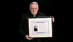 The Rev. John E. Rybolt, C.M., Vincentian scholar-in-residence, with the Vincentian Studies Institute's Pierre Coste Prize. He received the honor in part for his recently published seven-volume global history of the Vincentian community that dates back to its beginning in 1625. The award is named after the distinguished French Vincentian historian Pierre Coste, C.M., who worked during the first part of the 20th century. Coste is considered the father of modern Vincentian studies. (DePaul University/Jeff Carrion)