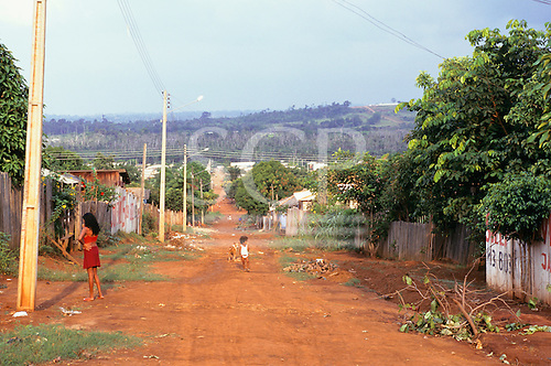 Altamira, Para State, Brazil. Dirt road through the town, two girls, a dog; houses.