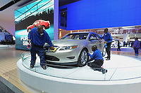 Workers at the Ford showroom dust off and polish a car at the Detroit Auto Show in Detroit, Michigan on January 11, 2009.
