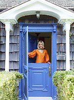 A portrait of designer Lorry Newhouse at her cottage door.