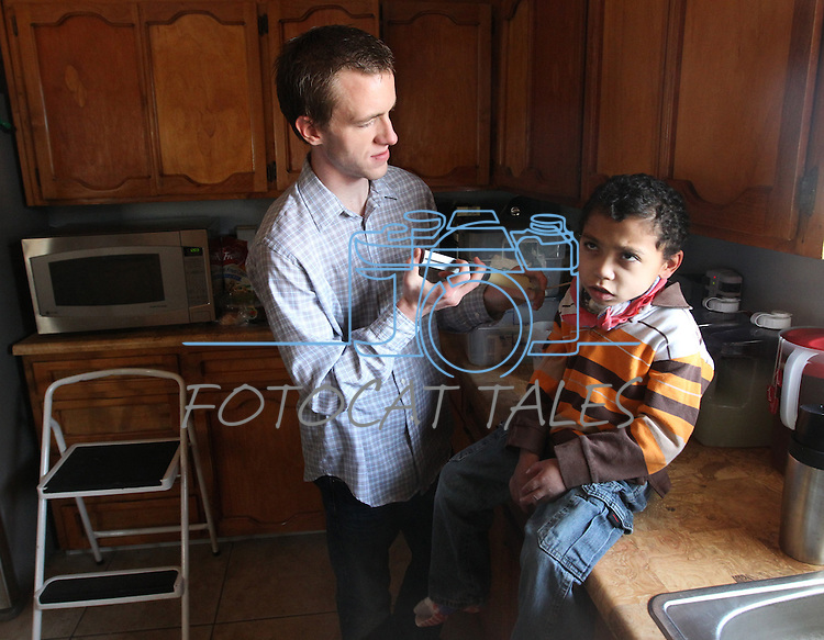 Jeremy Simon, 20, feeds his brother Joseph, 11, through a feeding tube on Sunday, Dec. 11, 2011, in their Mound House, Nev. home. Their parents, Merrill and Roberta Simon have adopted 21 special needs foster kids over the years. .Photo by Cathleen Allison