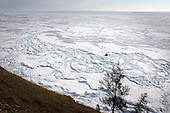 Our tent on the ice on Lake Baikal in Siberia, Russia, next to the cliff of Olkhon Island. (third day). .We are a group of five people: Justin Jin (Chinese-British), Heleen van Geest (Dutch), Nastya and Misha Martynov (Russian) and their Russian guide Arkady. .We pulled our sledges 80 km across the world's deepest lake, taking a break on Olkhon Island. We slept two nights on the ice in -15c. .Baikal, the world's largest lake by volume, contains one-fifth of the earth's fresh water and plunges to a depth of 1,637 metres..The lake is frozen from November to April, allowing people to cross by cars and lorries.