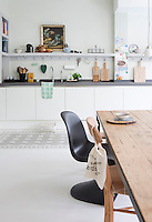 The modern kitchen/dining area is furnished with simple, functional units and a white tiled floor which reflects light around the open plan space