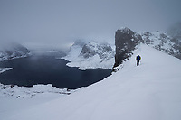 Hiker descends mountain pass towards Vindstad above Reinefjord in winter, Moskenesøy, Lofoten Islands, Norway