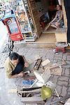 Hanoi, Vietnam, A carpenter works along a street sidewalk as a woman looks on. photo taken July 2008.