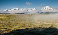 snow-capped Teton Mountains emerge from the fog at sunrise