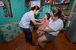Nirish Camporedondo, a student in the Mary Johnston College of Nursing in Manila, listens to the heartbeat of 4-year old Jewell Rae Tulauan, who sits on the lap of her mother, Raquel Tulauan, in their home in the Parola neighborhood of Manila's Tondo section. Camporedondo and other nursing students regularly visit the neighborhood to do health education and monitor the health of residents. The students also run a feeding program for neighborhood children.<br /> <br /> The nursing school is supported by United Methodist Women.