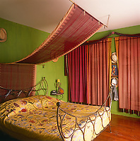 A green bedroom with red curtains and a canopy above an ornate metal bed. The bed has a yellow cover with a tree and floral pattern.