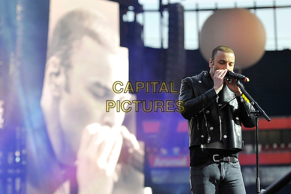 Chris Wolstenholme of Muse.Muse perform live in concert, Emirates Stadium, London, England, UK,.25th May 2013..music gig on stage performance performing half length playing harmonica microphone screen .CAP/MAR.© Martin Harris/Capital Pictures.