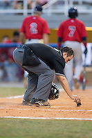 Umpire Garon Keuten cleans off home plate during the Appalachian League game between the Elizabethton Twins and the Kingsport Mets at Hunter Wright Stadium on July 9, 2015 in Kingsport, Tennessee.  The Twins defeated the Mets 9-7 in 11 innings. (Brian Westerholt/Four Seam Images)
