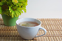 Cup of tea on bamboo with green flowers with white background