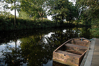 Boat tied to dock on the Ure river, Boroughbridge, North Yorkshire, England.