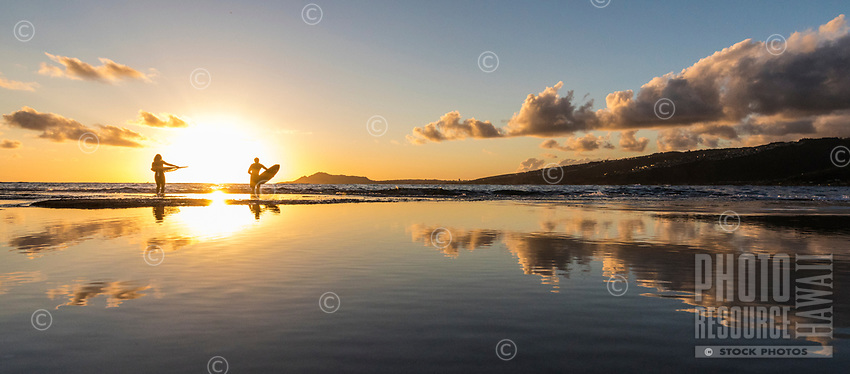 A couple heading out for an evening surf session in Maunalua Bay are reflected in tidal pools near Koko Head, East O'ahu.