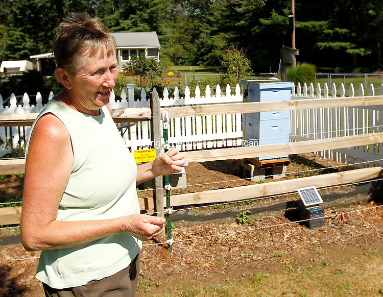 Terryville, CT-10 September 2012-091012CM13-  Susan Gray of Terryville talks about her beehive (shown in the background) at her home Monday afternoon in Terryville.   Gray and her partner, Kate Moran recently got into beekeeping, as they wanted pollinators for their beautiful gardens. Christopher Massa Republican-American